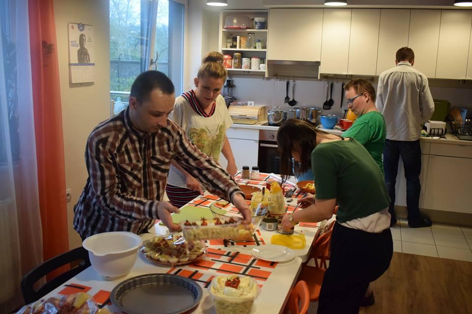 Podopieczni wraz z opiekunami w trakcie przygotowania posiłków wielkanocnych. Stoją w kuchni przy dużym stole.
