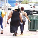 Na zdjęciu widoczne sa trzy bardzo otyłe kobiety idące ulicą w centrum miasta, Są odwrócone tyłem do zdjęcia.