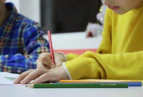 na zdjęciu znajduje sie rysujące dziecko z połprofilu, jest w źółtym sweterku, obok siedzi kolejne z niebieskiej koszuli w kratę