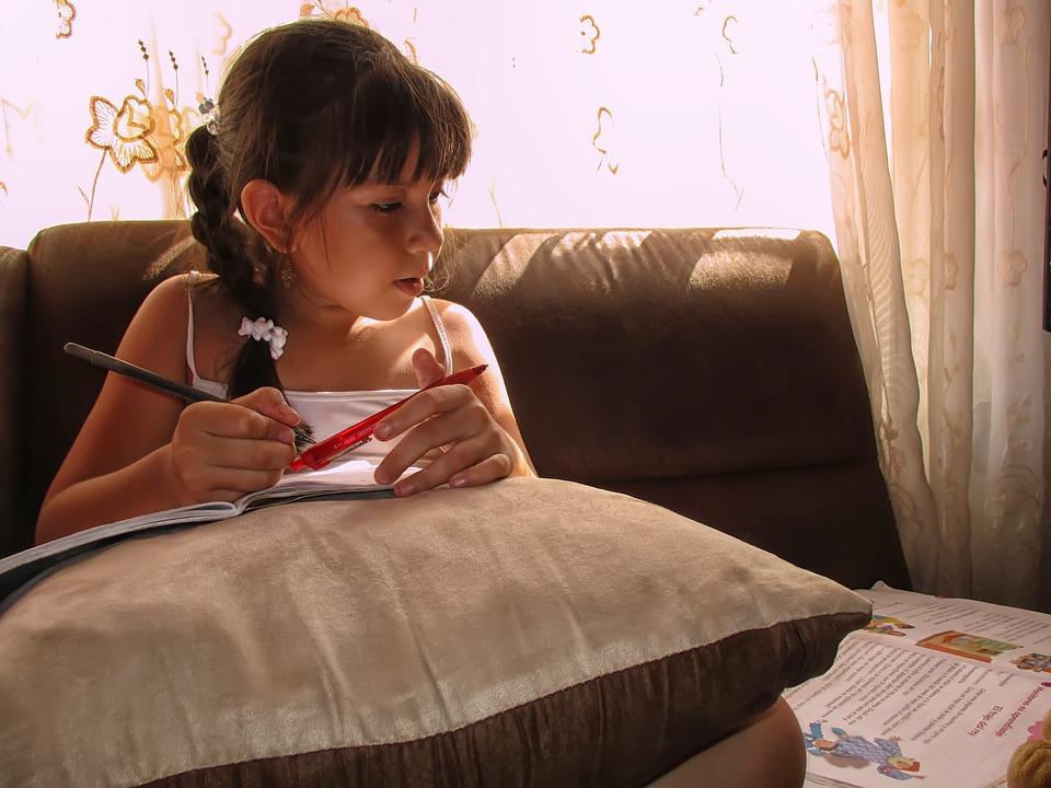 zdjęcie przedstawia dziewczynkę odrabiającą lekcje w domu. Siedzi na sofie z wielka poduszką na kolanach, na której trzyma zeszyt a obok leży książka, na która spogląda