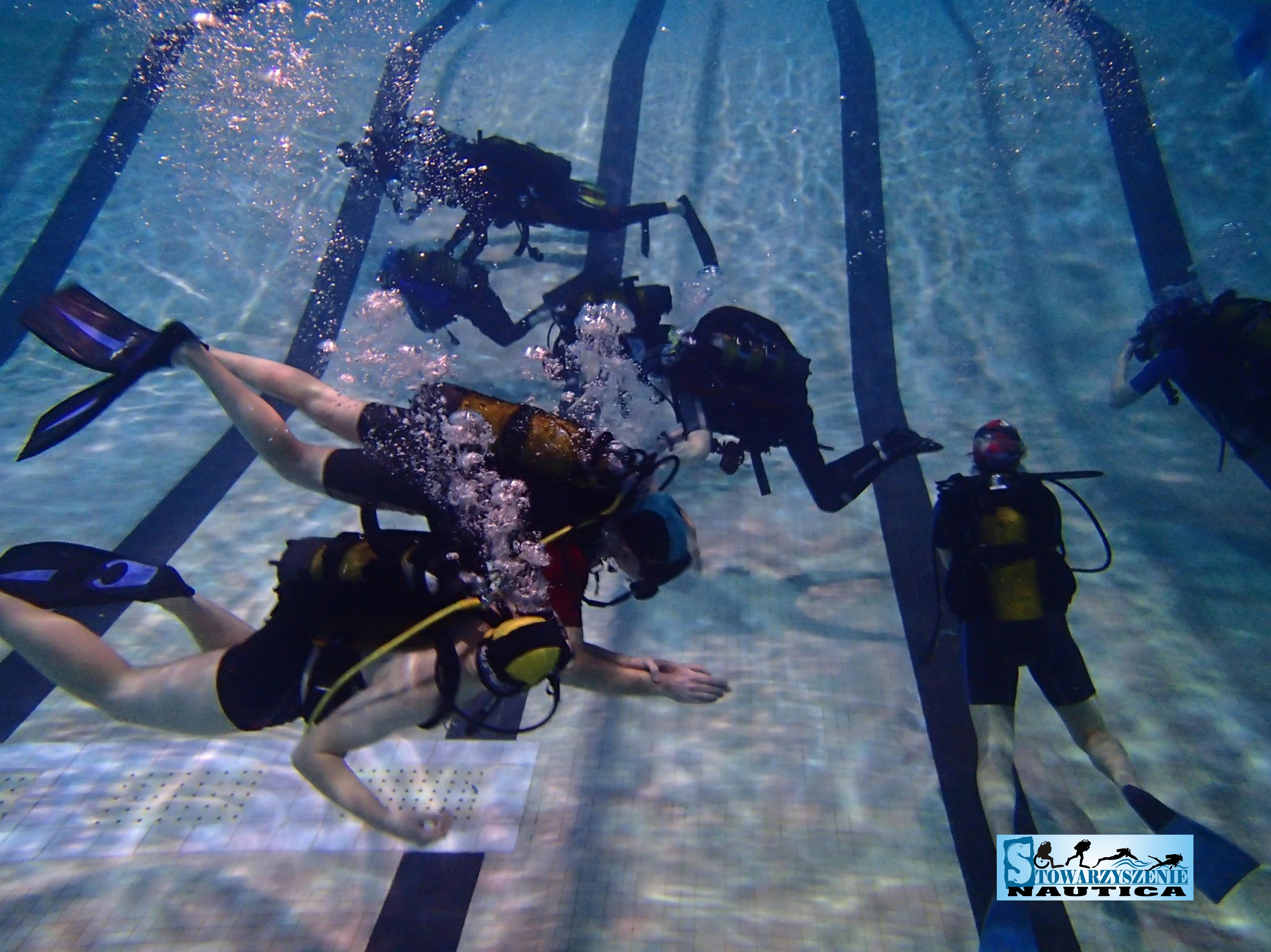 zdjęcie z zajęć kursowych na basenie widać na nich kilku nurków pływających na dnie basenu, na pierwszym planie niewidomy kursant (widoczny kontakt dotykowy).
