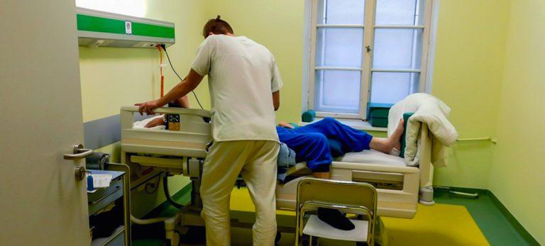 olsztyński budzik dla dorosłych. na zdjęciu widać pielęgniarza pochylającego się nad leżącym w łóżku pacjentem