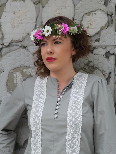 Angelika - modelka z protezą ręki, zdjęcie portretowe. Pozuje na tle ściany z kamieni, ma piękną szarą bluzkę ana głowie wianek