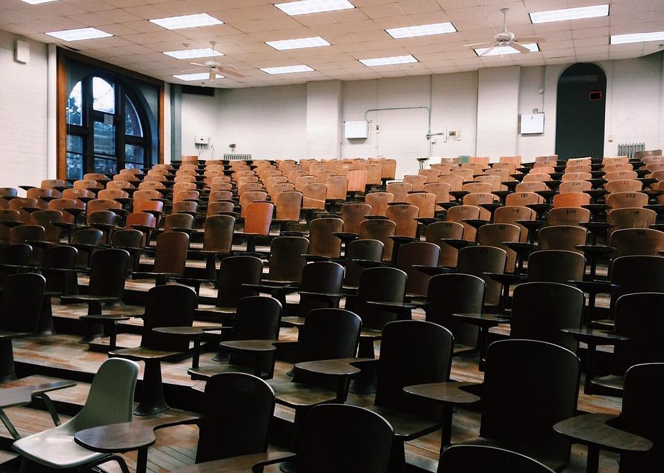 zdjecie przedstawia dużą, pustą salę wykładowa na uniwersytecie (aulę), Zdjęcie zrobione z prespektywy tablicy ukazuje puste drewniane krzesełka