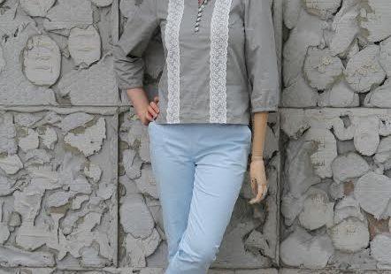Angelika - modelka z protezą ręki. Zdjęcie całej sylwetki. Pozuje na tle ściany z kamieni, ma piękną szarą bluzkę, jasne jeansy, ana głowie wianek