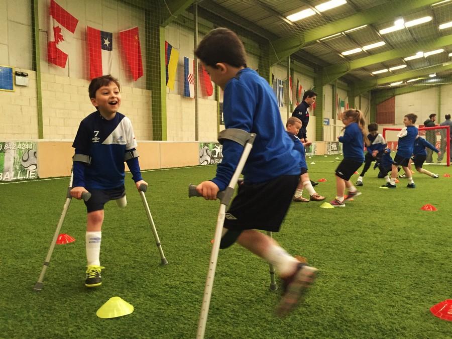 dwóch chłopców po amputacji nogi ćwiczących na boisku