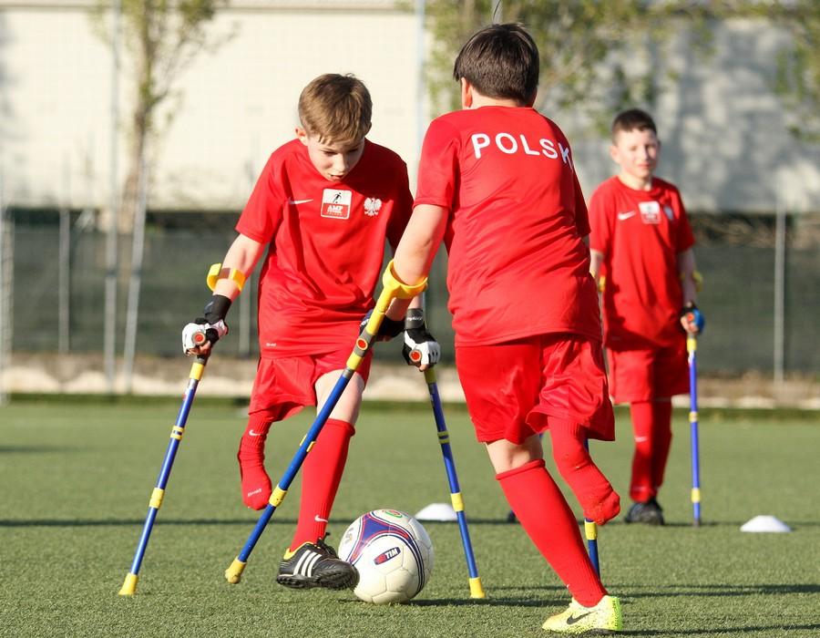 chłopcy rozgrywający mecz ampfutbolu w czerwonych strojach