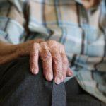 zdjęcie przedstawia kadr na dłonie. Dłonie spoczywają na kolanie, są pomarszczone i widać,że należą do osoby starszej i schorowanej. Zdjęcie przepełnia niewidoczny smutek