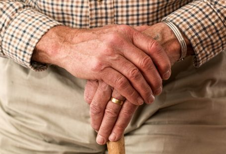 na zdjęciu widoczny jest kadr na dłonie starszego mężczyzny, podpiera sie na drewnianej lasce, na lewej dłoni ma obrączkę, koszulę w kratę i jasne spodnie