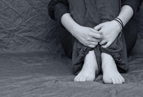 zdjęcie przedstawia kadr na skuloną postać kobiety. Jest w odcieniach czerni i bieli. Kobieta obejmuje swoje nogi. Nastrój zdjęcia jest nostalgiczny i depresyjny.