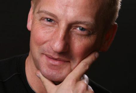 Zdjęcie przedstawia portret pana Leszka Skierskiego, kierownika Działu Promocji i Marketingu. Pozuje do zdjęcia z uśmiechem oraz dłonią dotykająca brody. Ubrany jest w czarną koszulkę, która współgra z czarnym tłem