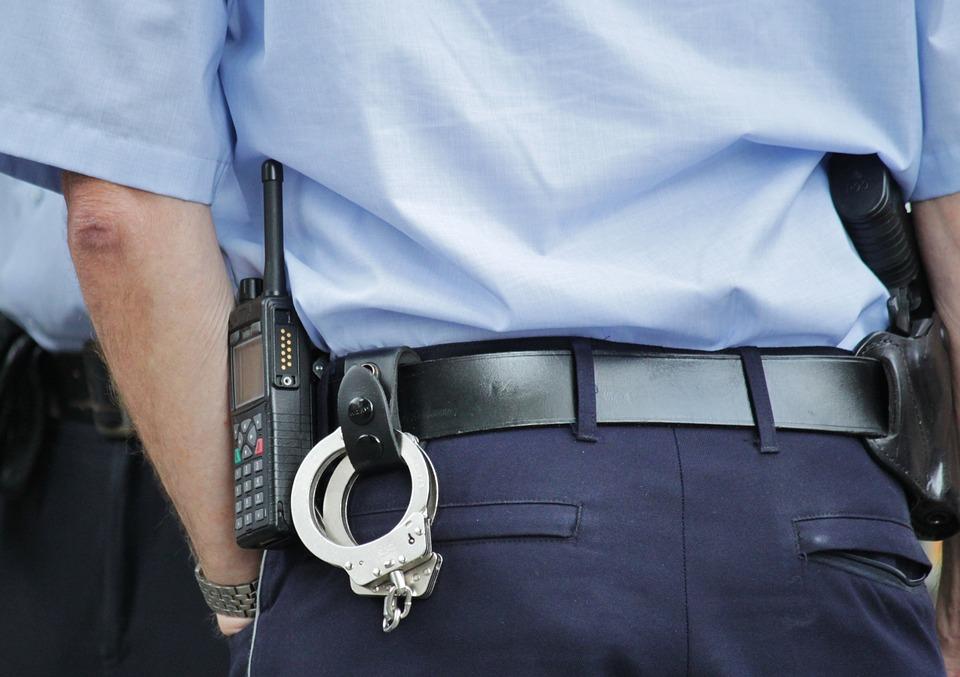 na zdjeciu znajduje sie policjant stojący tyłem do aparatu. Jest to kadr ukazujący zbliżenie na kajdanki i telefon, które trzyma przypięte do paska