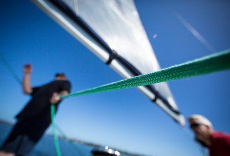 na zdjęciu widoczny jest żeglarz sterujący swą żaglówką, ostrośc skoncentrowana jest na linie, reszta jest lekko rozmazana