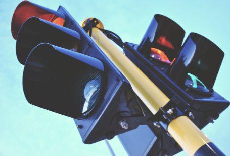 zdjęcie przedstawia sygnalizację świetlną z jednej strony dla pieszych, a z drugiej dla aut. Zdjęcie zrobione z dołu.