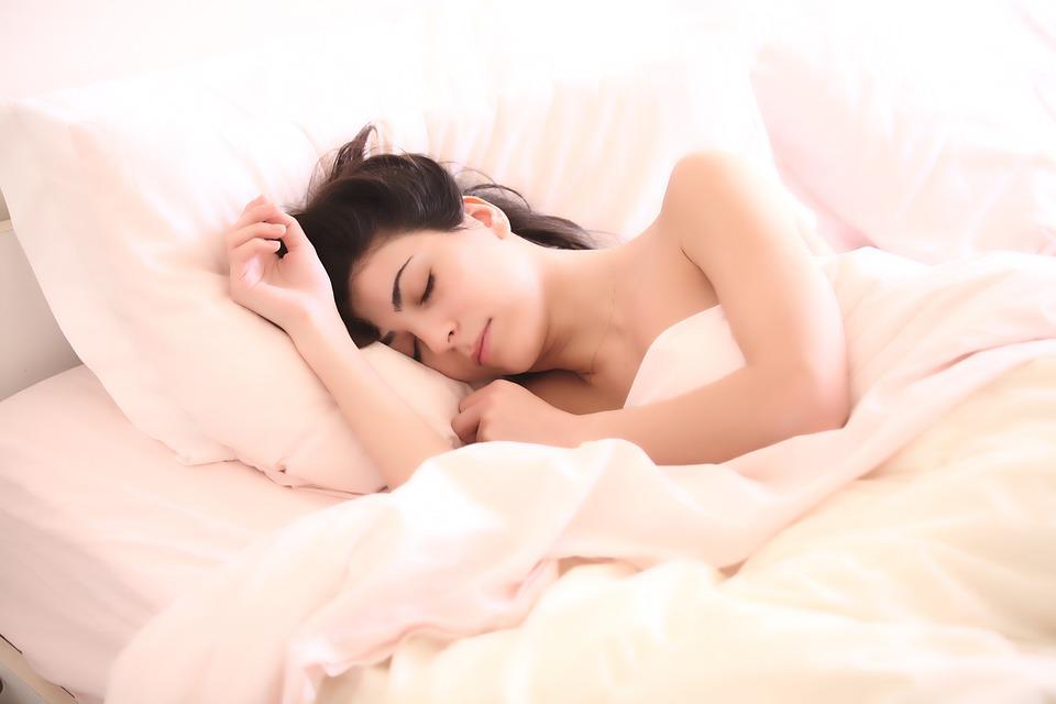 śpiąca kobieta w łóżku z białą pościelą