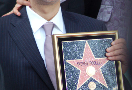 Andrea Bocelli trzymający nagrodę. Jest ubrany w garnitur
