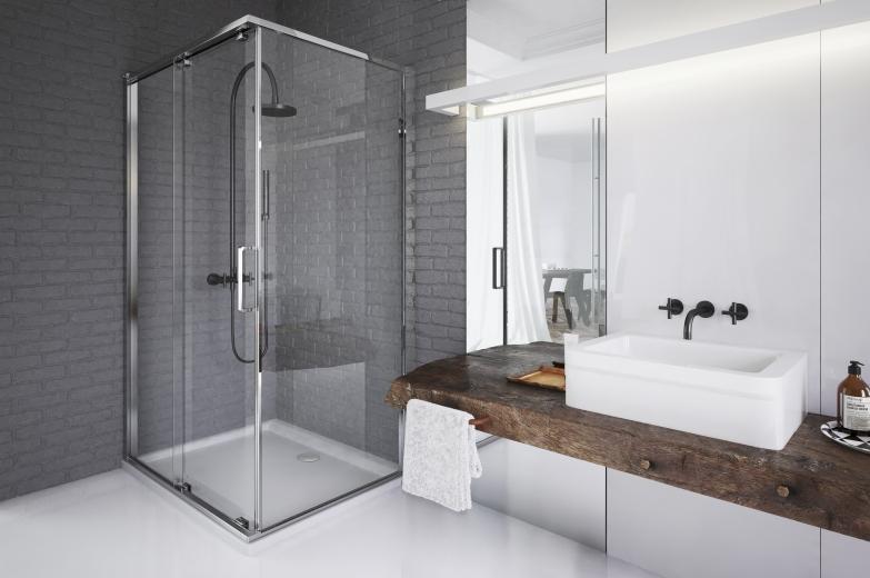 zdjęcie przedstawia aranżacje łazienki, szklany prysznic, białe meble pod umywalkę z grubym blatem z naturalnego drewna, białą podłogę i szare ściany