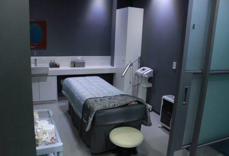 zdjęcie przedstawia puste łózko szpitalne z aparaturą i obok. Miejsce jest nowoczesne i schludne.