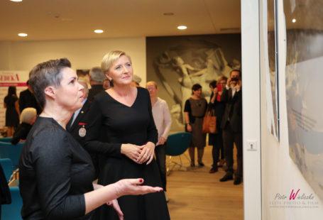 Na zdjęciu znajduje się Pani Jolanta wraz z Panią prezydentową Agatą Dudą. Zdjęcie zostało wykonane w trakcie trwania wystawy Kobieta z blizną, obie patrzą na to samo zdjęcie i rozmawiaja o nim. Pani Jolanta ma podniesioną prawą rękę, pani Agata zaplecione i spoczywające na talii. Obie sa dość poważne i skupione