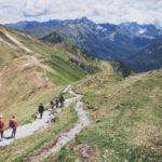 Zdjęcie ludzi spacerujących ścieżka górską, w tle cudowne widoki tatrzańskich szczytów
