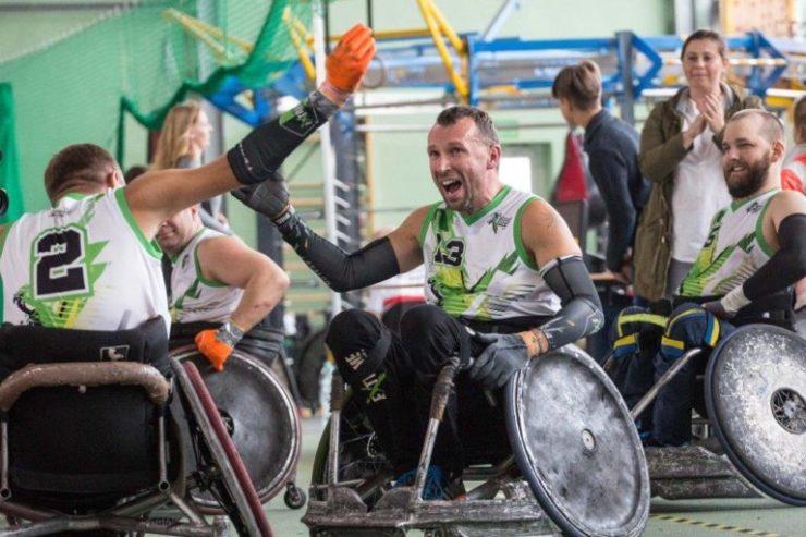 na zdjęciu znajduje sie trzech naszych zawodników tryumfujących wygraną w rugby. Są usmiechnieci, mają podniesione ręce, siedzą na sportowych wózkach inwalidzkich