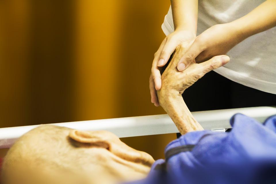 zdjęcie przedstawia chorego człowieka, jest to wykadrowana jego dłoń, która trzyma opiekunka, oraz kawałek twarzy, jest stary i najprawdopodobniej umierający. Leży w łóżku