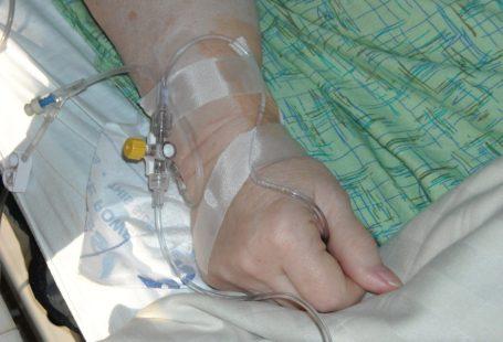 zdjęcie przedsawia kadr na kobiecą dłoń. Ma wenflon oraz plasrty na dłoni i jest podłączona do kroplówki. Widać, że jest w trakcie pobytu w placówce zdrowia