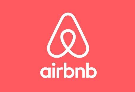 logo marki airbnb, czyli bardzo uproszczony samolot na koralowym tle z napisem airbnb