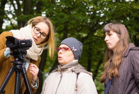 Ada Gąska w trakcie nakręcania filmu z osobami niepełnosprawnymi, wszyscy patrzą w aparat, są bardzo zainteresowani, ubrani są w ciepłe ubrania