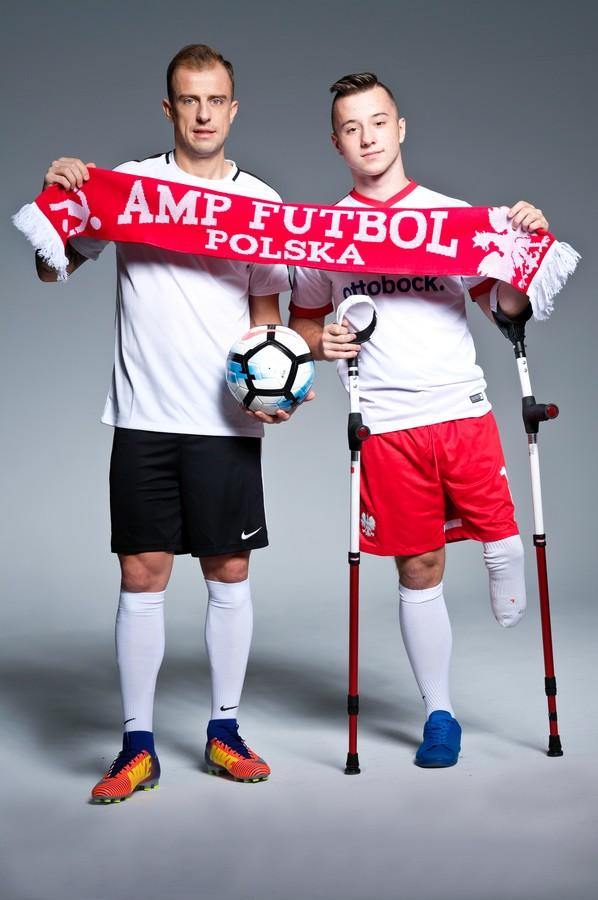 na zdjęciu pozuje Kamil Grosicki i Kuba Kożuch Amp Futbol Polska stoją na szarym tle w studiu, trzymają szalik amp futbol polska oraz piłkę