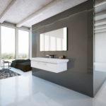 aranżacja minimalistycznej łazienki w odcieniach bieli i beżu, jest przestrzenna bez zbędnych rzeczy i kolorów, w centralym miejscy znajduje się wisząca przy ścianie duża umywalka nad nią ogromne kwadratowe lustro, a pod nią szafka