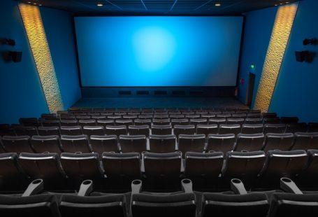 zdjęcie przdstawia salę kinową wraz z ekranem. Zdjęcie zrobione jest z najwyższego rzędu