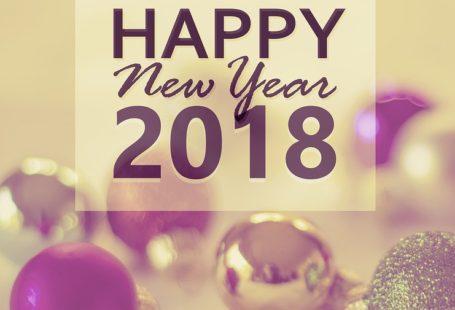 obrazek przedstawia rozmyte fioletowo srebrne bąbki a na nich napis happy new year 2018