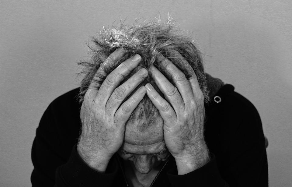zdjęcie przedstawia mężczyznę trzymającego obie dłonie na głowie, w geście załamania, nie widać jego twarzy, jedynie czoło, fotografia jest czarno-biała