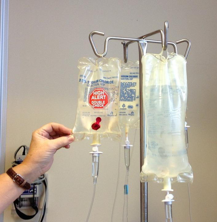 Zdjęcie przedstawia worki z płynem infuzyjnym służącym do podawania pacjentom chorym na raka, wiszą na wieszaku do kroplówek, jeden z worków dotyka czyjaś dłoń