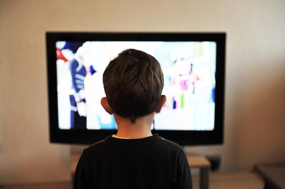na zdjęciu widoczny jest chłopczyk, który ogląda telewizję. Zdjęcie zrobione jest od tyłu, zatem nie widać jego twarzy.