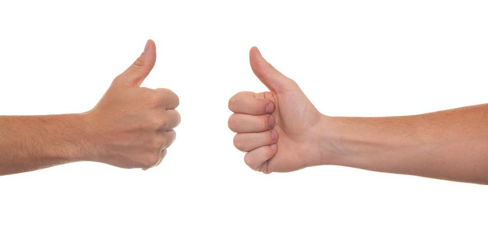 zdjęcie przedstawia dwie dłonie skierowane do siebie ułożone w pięść z wysuniętym kciukiem skierowanym w górę