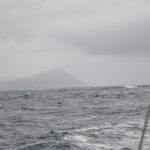 zdjęcie wykonane z jachtu w trakcie żeglowania, na horyzoncie widać tylko wodę a w oddali skaliste wzgórza