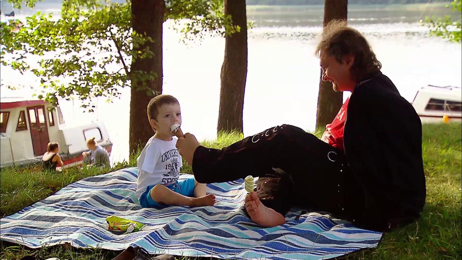 Kadr z filmu. Mężczyzna trzyma w stopach loda, którym karmi Stasia. Siedzą na kocu nad zalewem
