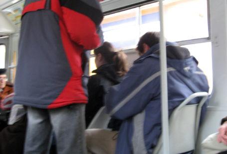na zdjęciu widoczna jest kontrola biletów. Pasażer siedzi na fotelu, a nad nim stoi kontroler sprawdzający bilet
