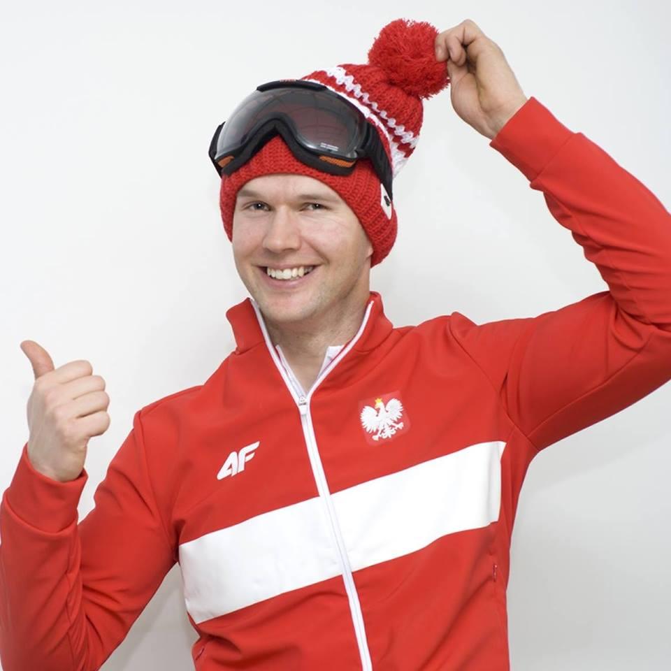 portret Igora Sikorskiego, ubrany jest w sportowy czerwony strój 4F, oraz czerwoną czapkę, uśmiecha się do zdjęcia i pokazuje kciuka