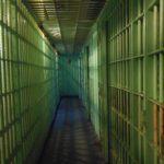 zdjęcie przedstawia wnętrze więzienia, jasnozielone kraty, wąski korytarz, zdjęcie jest przygnębiające i niepokojące