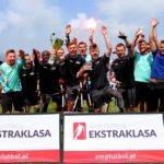 Amp Futbol Ekstraklasa: Gloria Varsovia wciąż niepokonana! Piłkarze cieszący się z wygranej, stoją na boisku w całej grupie, trzymają w rękach race