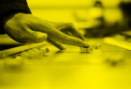 rysunek główny audycji czat czwórki, przedstawia dłoń sterującą sprzętem radiowym, jest w odcieniach czerni i żółci