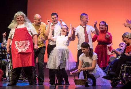 fot. Dawid Linkowski, zdjęcie jest bardzo wesołe i kolorowe, przedstawia aktorów na scenie w trakcie odgrywania sztuki, są wśród nich osoby na wózku inwalidzkim , osoby z zespołem downa, mają na sobie śmieszne stroje i peruki, fartuchy oraz wielkie uśmiechy