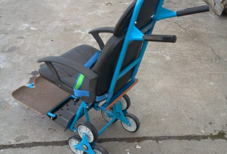 """Zdjęcie przedstawia pierwszy egzemplarz krzesełka, stworzonego z """"części składowych z Marketów"""". Wygląda podobnie do klasycznego wózka inwalidzkiego, lecz różnią go koła. W wózku inwalidzkim koła znajdują się po dwóch stronach, są bardzo duże, a w przypadku krzesełka są to aż trzy kółka po prawej jak i po lewej stronie oraz jedno po środku z przodu Są małe, jak w wózkach dziecinnych. Z przodu krzesełka znajduje się wysuwana i składana część na nogi"""