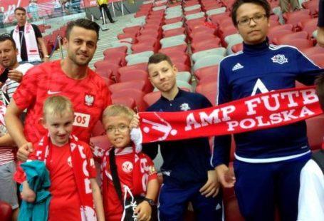 Łukasz Fabiański pozuje z czterema chłopcami trzymającymi szalik z napisem AMPfutbol