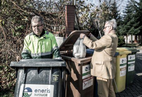 zdjęcie przedstawia dwóch mężczyzn segregujących śmieci
