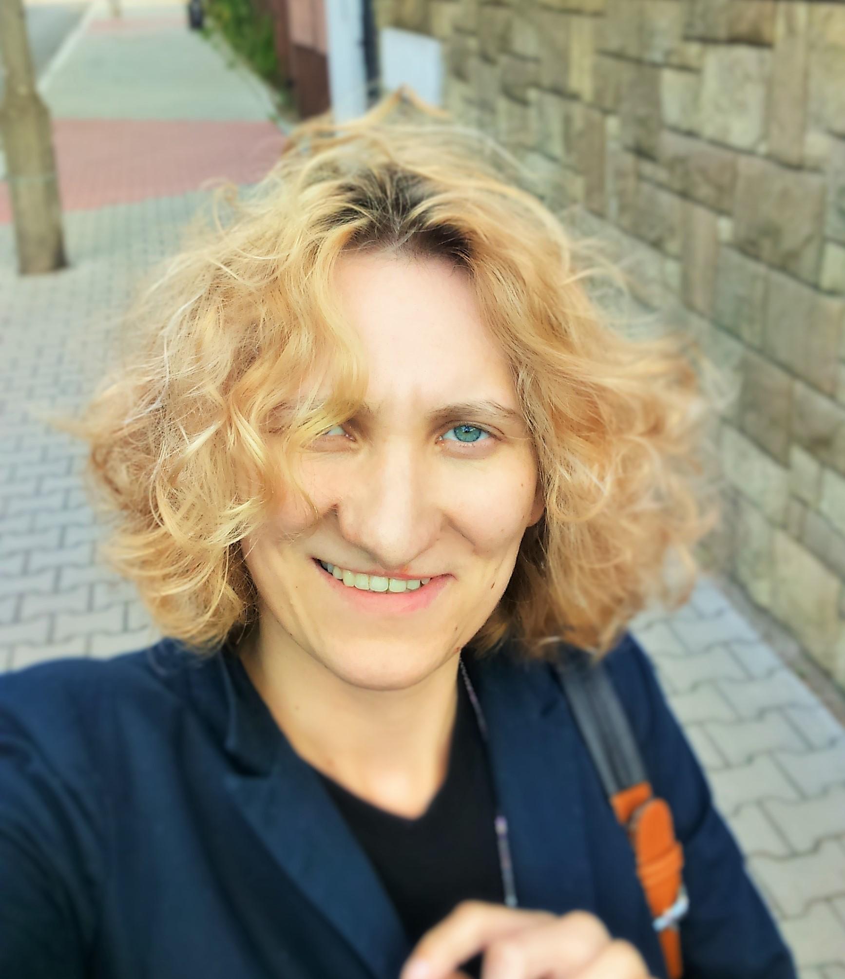 Zdęcie selfie Pani Anety, jest na nim bardzo uśmiechnięta, na twarz opada burza jasnych blond loków, ubrana jest w granatową marynarkę