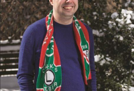 na zdjęciu widzimy uśmiechniętego Filipa Zagończyka, pozującego z przewieszonym na szyi szalikiem Legii,